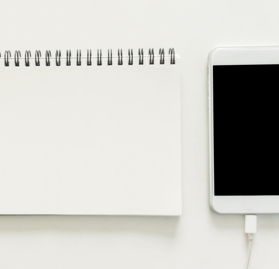 Smartphone e bloco em branco sobre mesa